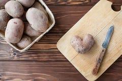 Heart shaped potato on the plank Royalty Free Stock Photo