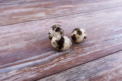 Heart shaped quail eggs. Quail eggs on the brown wooden table Stock Image
