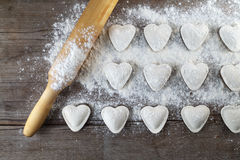 Heart shaped ravioli. Heart shaped dumplings, flour and rolling pin on wooden background. Cooking ravioli. Top view Stock Photos