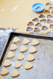 Heart shaped raw cookies on metal baking tray, selective focus Stock Photos