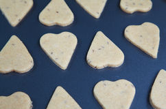 Heart shaped raw dough cookies with caraway on metal baking tray Royalty Free Stock Photography
