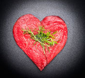 Heart shaped raw meat with fresh herbs on black chalkboard background, top view, close up Royalty Free Stock Image