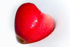 Heart-shaped red apple. Close-up of heart-shaped red apple on white snow Stock Photo