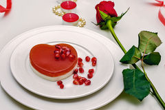 Heart shaped red cake on a white plate. Delicious dessert for Valentine`s Day Romantic dinner Royalty Free Stock Photo