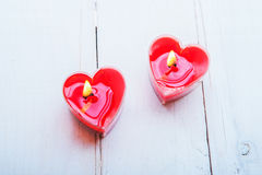 Heart-shaped red candles on white wooden background. Heart-shaped red candles on white table Royalty Free Stock Photography