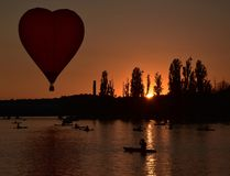 Heart shaped red Hot air balloon flying. In the air above Lake Burley Griffin in the early morning, as part of the Balloon Spectacular Festival royalty free stock images