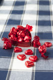 Heart shaped red metal box with sweet chocolates. Heart shaped red metal box full with many sweet chocolates. Closeup Royalty Free Stock Photography