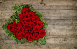Heart shaped red roses bouquet on rustic wooden background Stock Photography