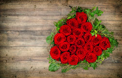 Heart shaped red roses bouquet on wooden background. Valentines Royalty Free Stock Image
