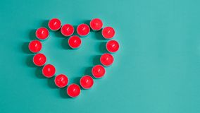 Heart shaped red tea light candles. Red tea light candles forming a heart shape on vintage green background stock images