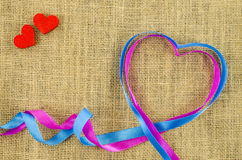 Heart shaped ribbon on linen background Stock Photos