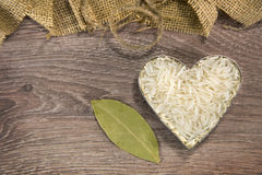 Heart shaped rice on wood stock image