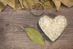 Heart shaped rice on wood. Background stock image