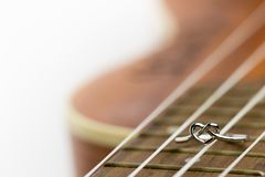 Heart shaped ring laying on ukulele string. The concept of a musician lover. Copy space can be used to write articles about Valentine`s Day stock images