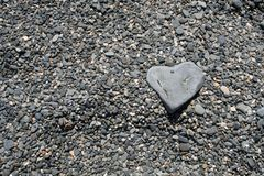 Heart shaped rock on beach. Heart-shaped rock on a grey pebbled beach. Taken in Kennebunkport, Maine Stock Photo
