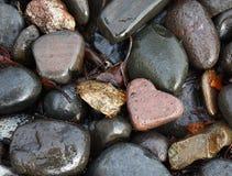 Heart Shaped Rock In Wet Rocks. Pink heart shaped rock nestled in wet rocks stock photography