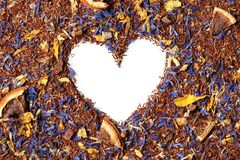 Heart shaped from rooibos tea with cornflower and orange slices on white background. Royalty Free Stock Photos