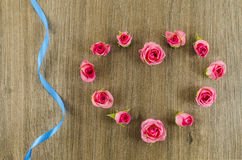 Heart shaped rose flower and ribbon on wooden background Stock Images
