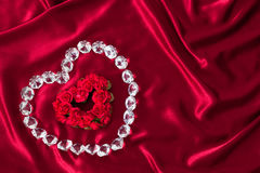 Heart shaped Roses outlined with diamonds on red satin (P) Stock Photography