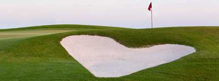 Heart shaped sand bunker in front of golf green. Heart shaped sand bunker on golf course illustrating love for game of golf. Sized with ratio of 851 x 315 pixels Stock Photos
