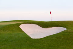Heart shaped sand bunker in front of golf green. Heart shaped sand bunker in front of red flag of golf hole on beautiful course at sunset illustrating love for Stock Images