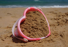 Heart shaped sandcastle bucket. Childs heart-shaped sandcastle bucket on the beach royalty free stock photography