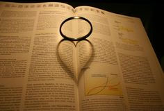 Heart shaped shadow. Shadow of a lens on a book stock illustration