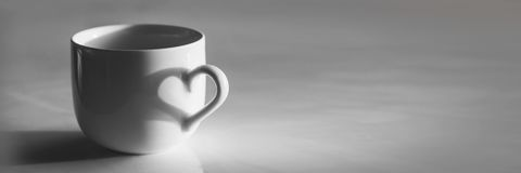 Heart shaped shadow on a coffee cup, black and white. Heart shaped shadow on a coffee cup in black and white royalty free stock photography