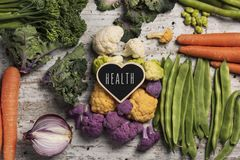 Raw vegetables and text health. A heart-shaped signboard with the text health written in it, placed on a pile of some different raw vegetables, such as stock photo
