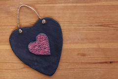 Heart shaped slate on wooden background. Stock Image
