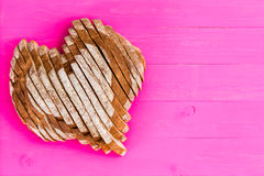 Heart shaped sliced bread on pink background stock photos