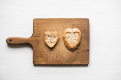Heart-shaped slices of bread on old cutting board love concept Stock Image