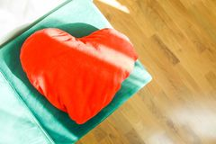 Heart shaped small decorative pillow on soft green pouffe. Modern interior cozy design element royalty free stock images