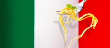 Heart shaped spaghetti over the Italian flag. Heart shaped spaghetti garnished with fresh basil hanging from a silver fork over the Italian flag with copy space stock photo