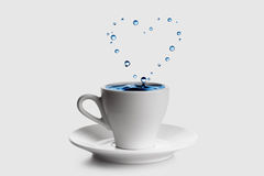 Heart shaped splash in white coffee cup Royalty Free Stock Images