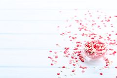 Heart shaped sprinkles. In glass bowl on wooden table stock photo