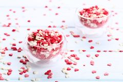 Heart shaped sprinkles. In glass bowls on wooden table stock photo