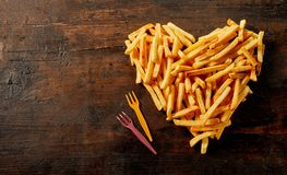 Heart shaped still life of French fries. Pommes frites or potato chips viewed from above on vintage wood with copy space and plastic forks royalty free stock photography
