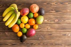 Heart-shaped still life of mixed tropical fruit. Heart-shaped still life of mixed healthy fresh tropical fruit with bananas, mango, orange, lemon, lime, avocado royalty free stock images
