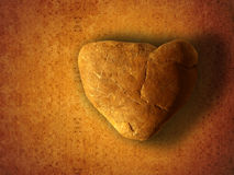 Heart-shaped Stone. A heart-shaped stone on a yellowed background Royalty Free Stock Images