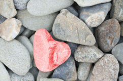 Heart shaped stone painted on red. In a pile of stones Stock Images
