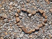 Heart shaped stone. On pebble background Royalty Free Stock Photo