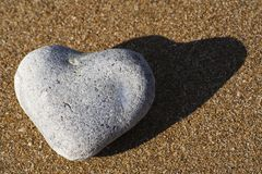 Heart shaped stone on a sandy beach Stock Photo