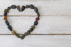 Heart shaped stone, small pebbles arranged as a heart on white w Royalty Free Stock Photos