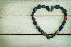 Heart shaped stone, small pebbles arranged as a heart on white w Stock Photos