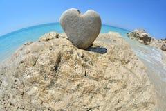 Heart shaped stone on white rock stock photo