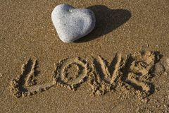 Heart shaped stone and the word love on a beach Royalty Free Stock Image