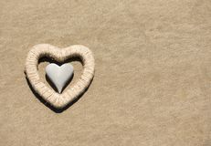 Heart shaped stone on yellow sand, beach background Royalty Free Stock Image