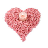 Heart shaped stones and candle. Lit candle in the middle of pink stones shaped like a heart Stock Photo