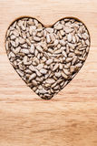 Heart shaped sunflower seeds on wood surface Stock Images
